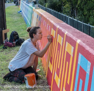 Assistant Aime Polivka painting on wall