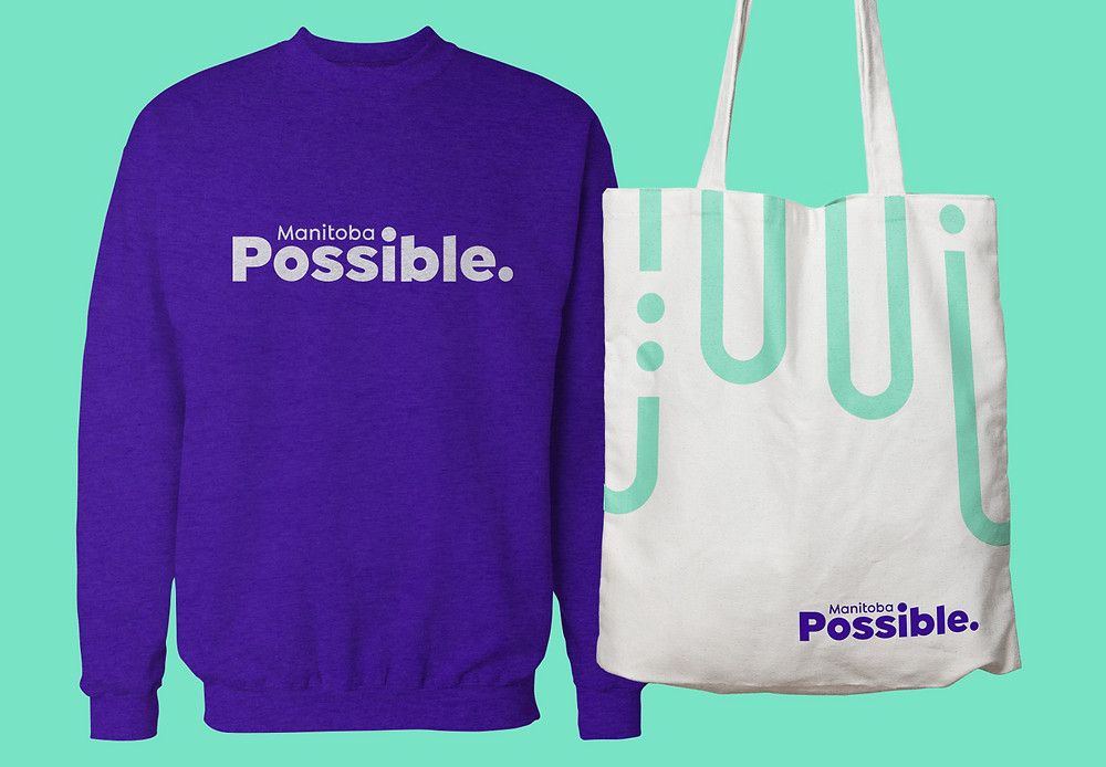 Manitoba Possible logo displayed on a sweatshirt and a tote bag.