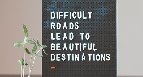 A sign that reads Difficult Roads Lead to Beautiful Destinations to support articla about Mergers and Aquisitions and how M&A Post Merger Integration is getting harder