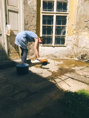 Lucia Zachariášová ekologicky horkou vodou likviduje plevel v zámecké dlažbě.