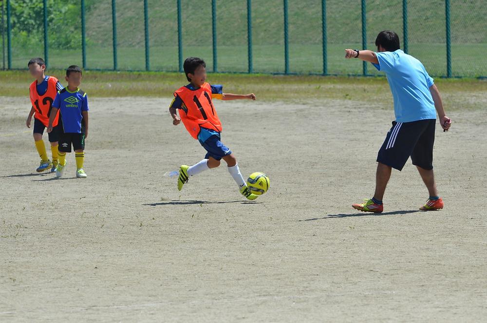 グラウンドでボールを追う子供たち