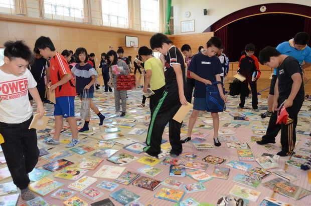 知小2018-床に並べられた本を選ぶ子供たち