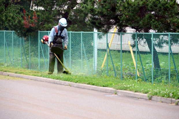 知小2018-熱い中、重装備で草刈りをしてくれる公務補さん。