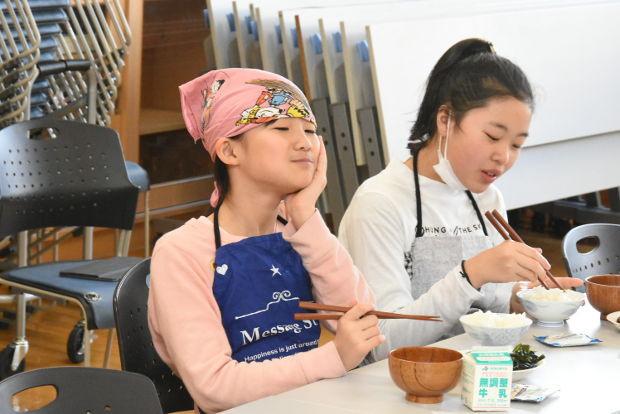 知小2019-5年生米作りの収穫祭でご飯を美味しそうに食べる子供
