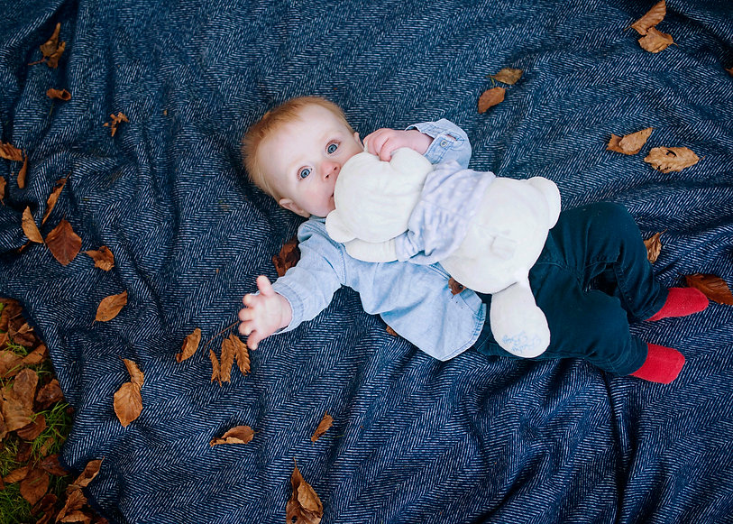 baby boy on a blue blanket surrounded by autumn leaves