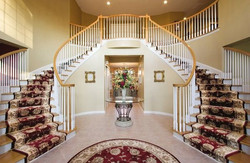 Beautiful-Flower-Decorating-the-Enty-Space-with-Curve-Staircases-and-Stairs-Carpet-Runner-near-Round