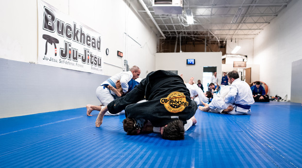 people sparring with buckhead jiu jitsu sign in background