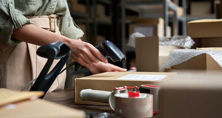 Warehouse worker scanning a package at an e-commerce fulfillment center