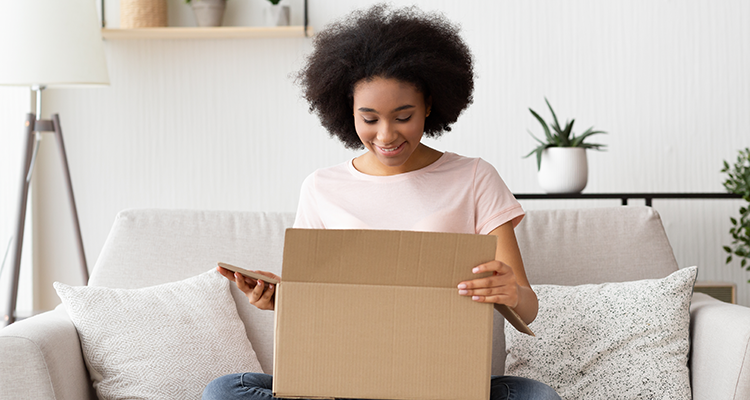 Young woman on couch opens a package that she's received in the mail