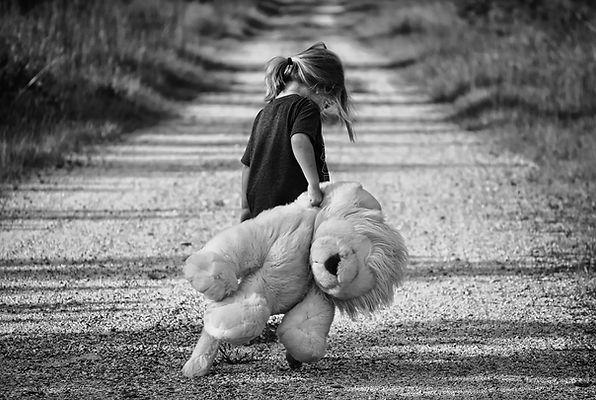 photo noir et blanc d'une petite fille qui traine sa grande peluche sur un chemin. photo libre de droits.