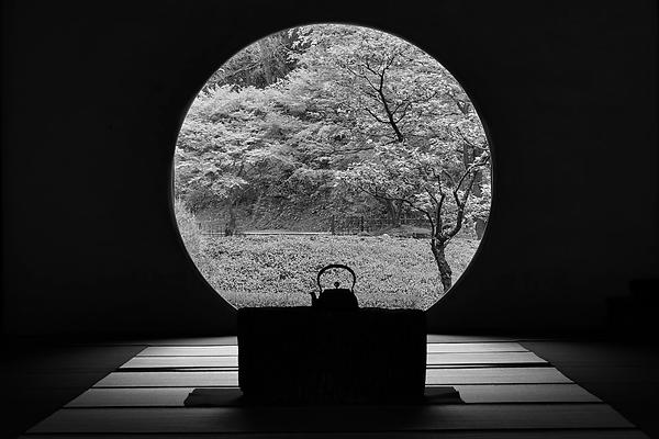 Sur des tatamis, ambiance japonaise, table basse avec une théière posée dessus en contrejour, et en arrière fond une grande fenêtre ronde qui donne sur un paysage d'arbres, le tout en noir et blanc.