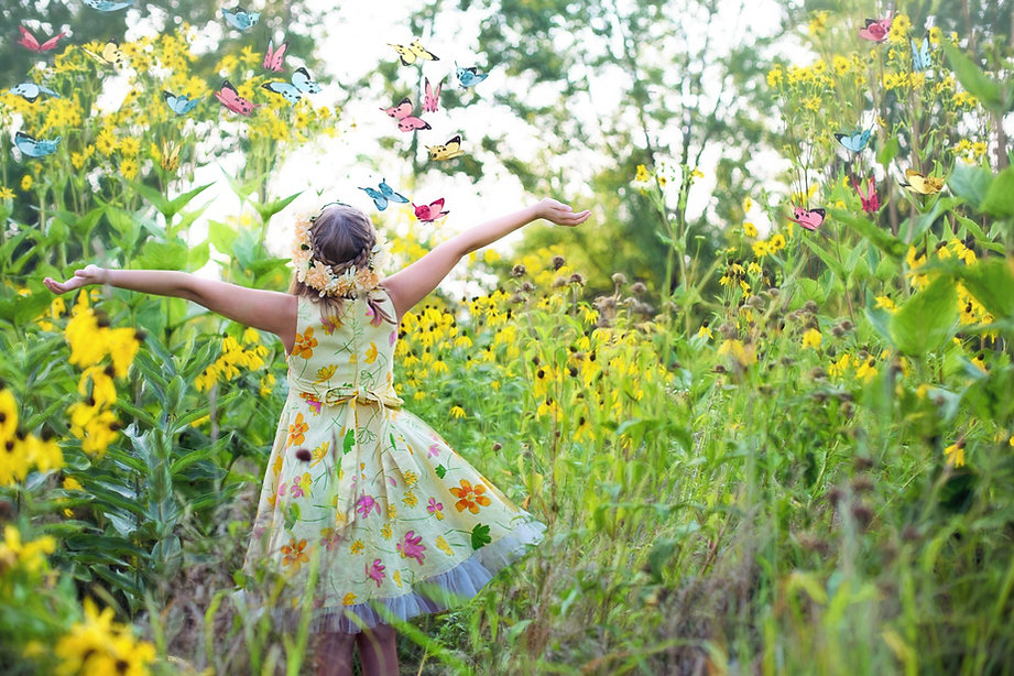 En pleine campagne, jeune fille de dos les bras en lair avec des papillons tout autour, robe jaune paille avec des fleurs.