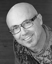 Portrait noir et blanc de Luc Pouget souriant avec des lunettes.