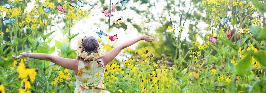 Photo couleur d'une petite fille de dos avec une couronne de fleurs, les bras tendus vers le ciel en pleine campagne et entourée de papillons.
