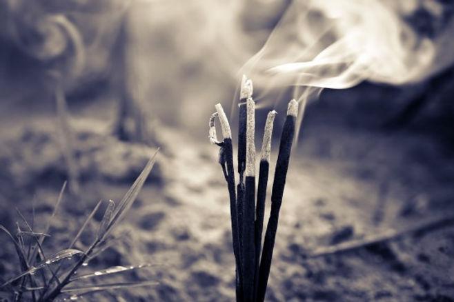 photo sépia de plusieurs batons d'encens qui brulent.