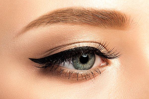 Close up view of gray woman eye with beautiful golden shades and black eyeliner makeup. Cl