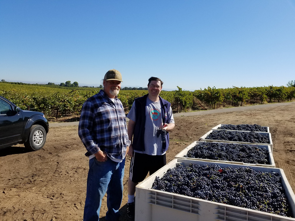 Gregg Lewis hands off his grapes to winemaker Steve.
