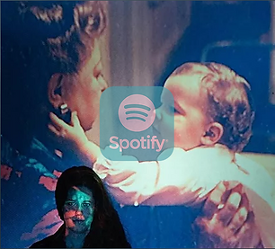 Long haired, brunette female musician sitting in the dark with a projector image over her, featuring herself as a baby in her grandmother's arms, reaching out and touching her earring