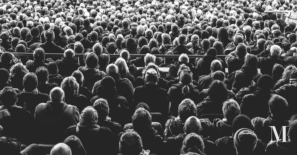 an audience seen from behind in black and white