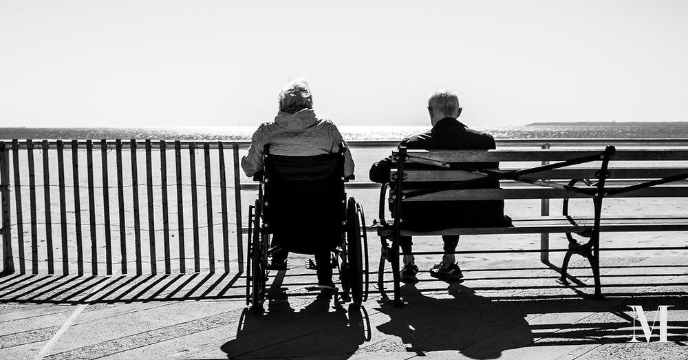 Woman in a wheelchair and man on a bench look out to sea