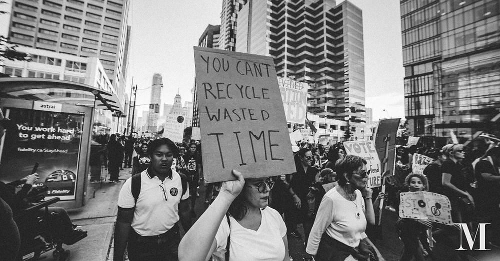 """Protesters, one holding a sign that reads """"You can't recycle wasted time"""""""
