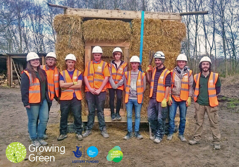 A team photo in front of the completed straw bale structure