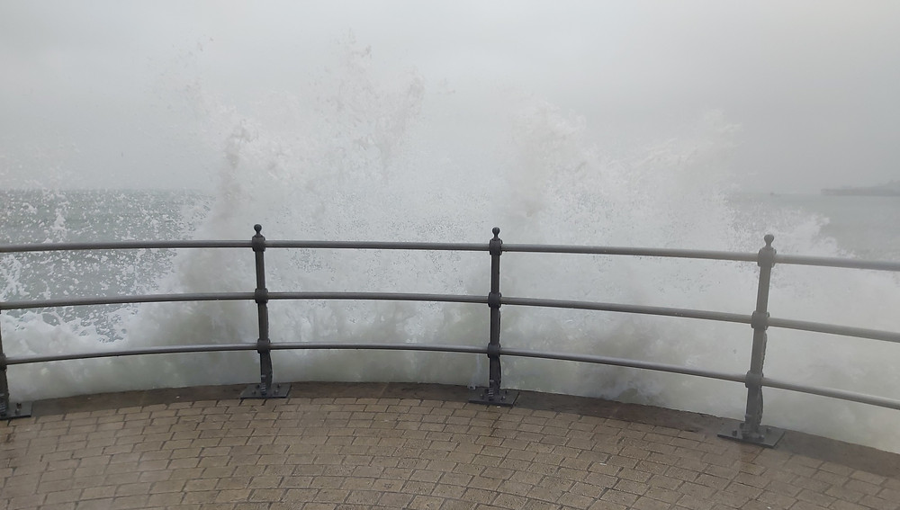Waves crashing against the sea wall in Swanage