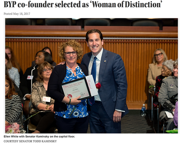 """Headline """"BYP co-founder selected as woman of distinction"""" image shows two people standing and posing for a photograph in a crowded room."""