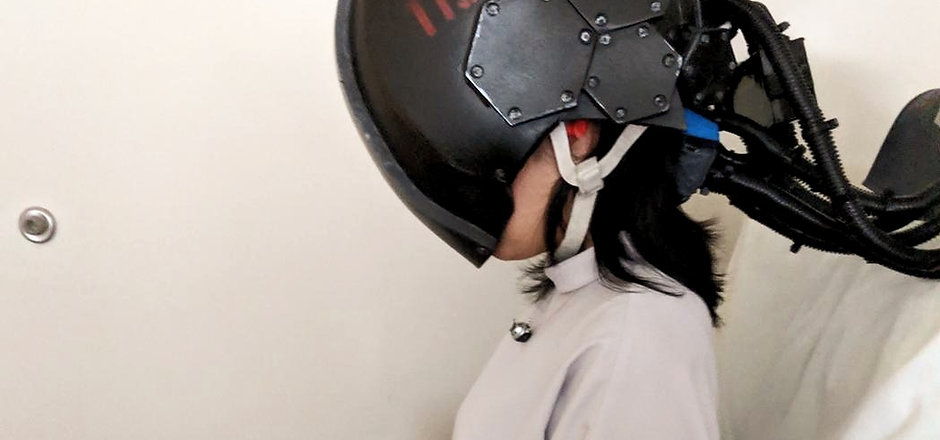 A woman wearing a helmet that covers her face and head, with several cables emerging from the back.