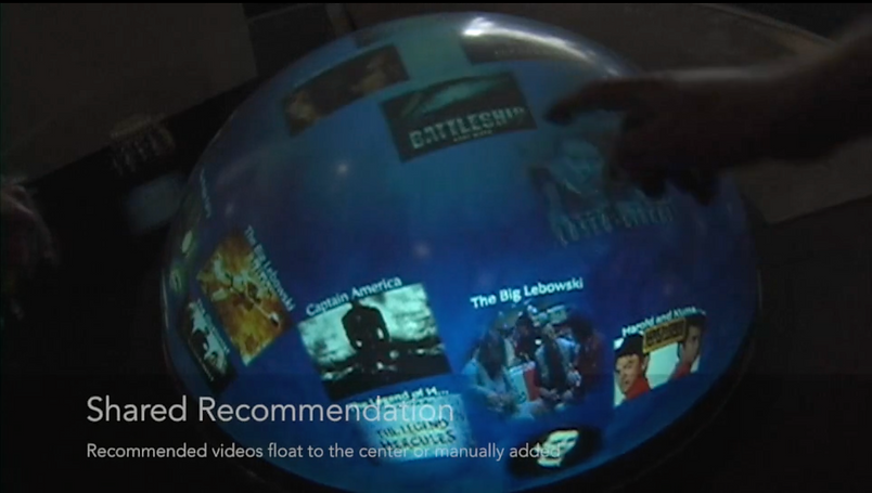 A ball-shaped touched display showing various movie posters.