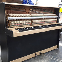 Upright Piano restoration with an all black keyboard and open front.