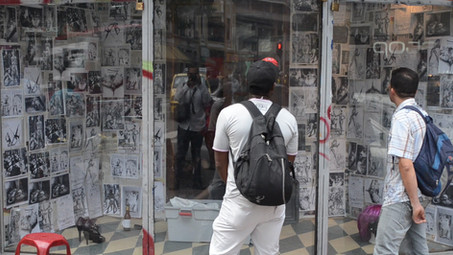 An external view to one of the showcases of the event holding the images, objects and devices that the BDSM collective brought for their actions as part of the bailata queer. The showcases allowed a connection in between the inside and outside, pedestrians and travelers were caugh participating as active viewers and voyeurs of this space.