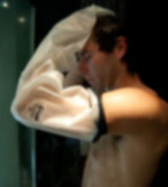 man in shower wearing a full arm limbo waterproof protector