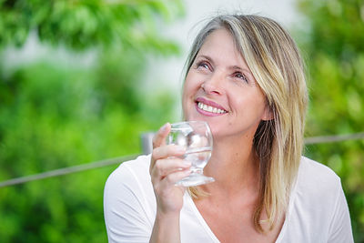 Smiling mature woman with water glass in her hands.jpg