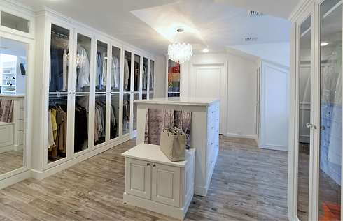 Dressing Room with chandelier, hardwood floors, glass door closets and center island.