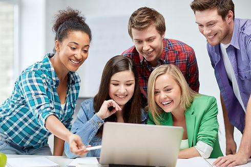 5 students surrounding a laptop on a desk
