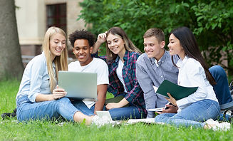 5 students sitting on grass looking at a laptop