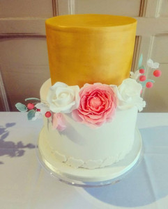 Beautiful gold and white cake with flora