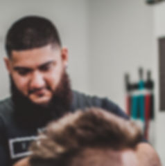 Ricardo Chavez giving a client a brand new haircut in his Revamp Barbershop