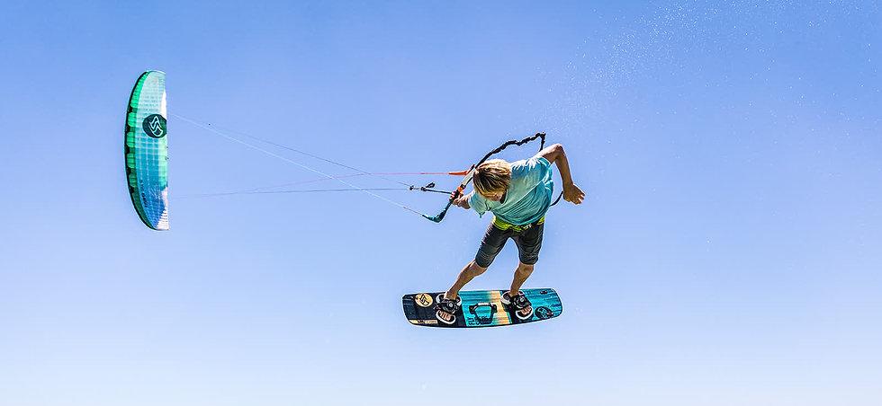 Kitesurfen auf Fehmarn. Kitesurfer mit Flysurfer Kite springt. Kitesurfen lernen auf Fehmarn bei der Kiteschule Fehmarn Kitetrainer.