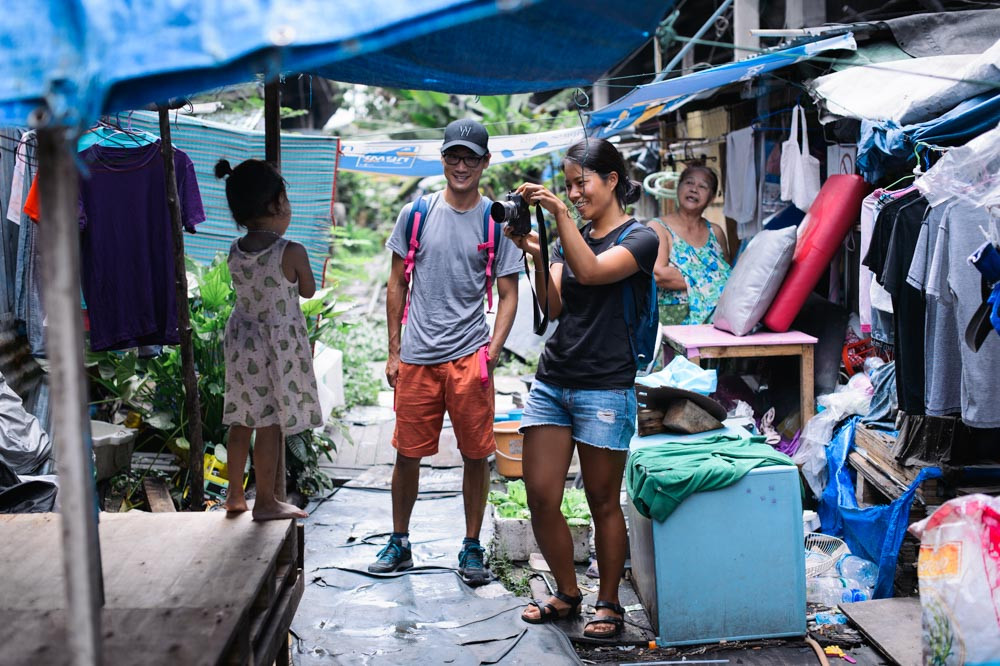 Young couple taking photos at Khlong Toei, Bangkok Thailand
