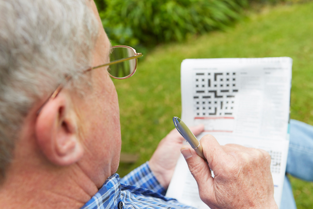 senior man doing crossword puzzle in yard
