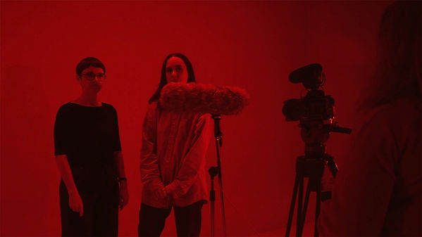Two women stand facing a video camera, while a third woman stands behind the camera watching them. There is a red filter over the image.