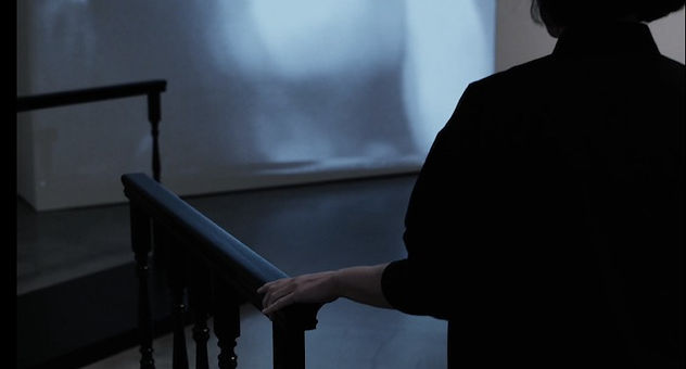 Frances Barrett, her back facing the camera, touches a sculpture by Tom Burr. This sculpture is a black hand rail that leads into the middle of the gallery. Another hand rail sculpture can be seen in the background.