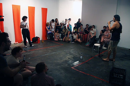 This image depicts a gallery space filled with an audience along two sides of the room. Two performer stand opposite each other, each holding microphones. Red stripes are painted down one side of the wall behind the female performer. There ground is littered with empty crates, puddles of water, empty bottles and banana peels.