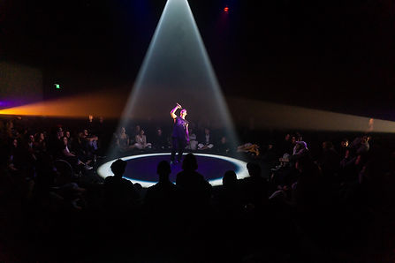 A live performance event in a theatre with an audience seated in the round. In the centre of the audience, under an intense purple spotlight, a performer Marcus Whale, sings into a microphone. His head is tilted upward.