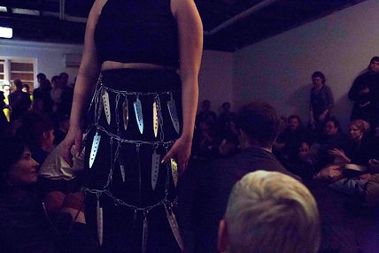 A gallery room filled with a seated audience, hapharzardly spaced around the room. A central performer, Leilah El Rayes, is central to the image. She wears a skirt made of silver knives that hang of silver chains. Her head is cropped out of the image.