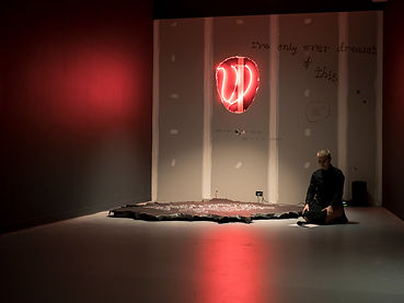Inside a small gallery space a performer, Athena Thebus, crouches on the ground with a microphone and script in front of them. Their head is lowered. A large neon light in the shape of a tongue protrudes from the wall behind them.