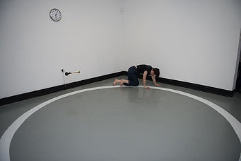 This image depicts a small gallery space with a white circle painted on the floor. A performer, Frances Barrett, is on all fours crawling along this line. There is a clock hung on the wall above her and a clown horn mounted on the wall at the level of her hunched shoulders.