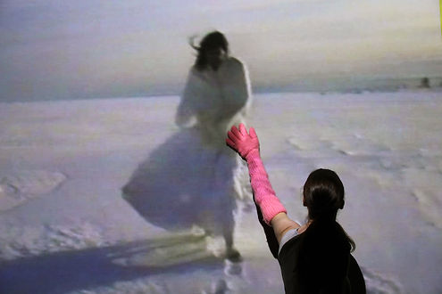 Frances Barrett wears a pink knitted glove that extends to her shoulder. She faces away from the camera, reaching up a wall where a video of Mike Parr is projected. He is performing in the snow, dressed as a bride. Her gloved fingers touch the illuminated figure of Parr.